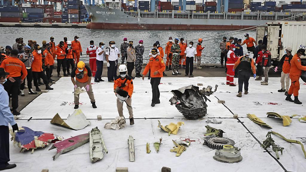 Trümmerteile werden im Hafen Tanjung Priok zur Inspektion ausgelegt. Foto: Dita Alangkara/AP/dpa