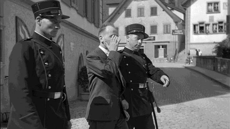 Polizisten bringen Hans Vollenweider zum Kantonsgericht Obwalden, 1940.