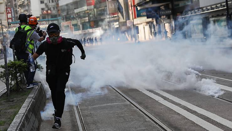 Nach dem Tränengas-Einsatz in Hongkong zerstreuten sich die Demonstranten, viele zogen in Richtung Stadtzentrum weiter, einige warfen mit Steinen.