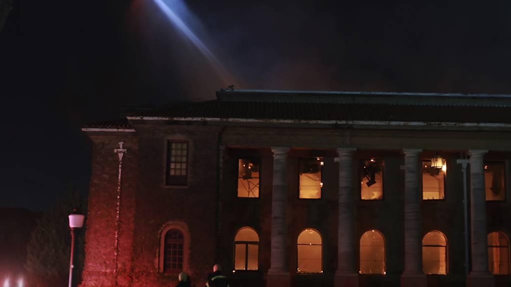 Feuerwehrleute löschen die Flammen in der  Jagger-Bibliothek an der Universität von Kapstadt. Ein Waldbrand, der an den Hängen vom Tafelberg wütete, griff auf die Universität über.