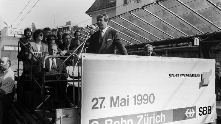 Bundesrat Adolf Ogi eröffnet am 17. Mai 1990 im Bahnhof Stadelhofen in Zürich - zehn Tage vor dem eigentlichen Start - mit einer Rede die S-Bahn und den Zürcher Verkehrsverbund (ZVV).