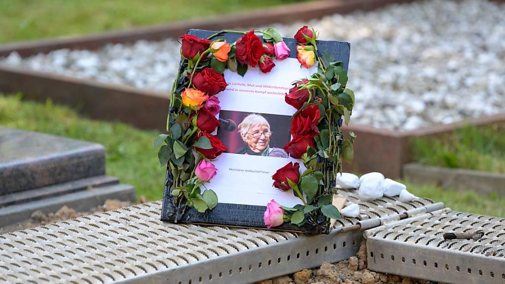 Ein Schild mit einem Foto von Esther Bejarano steht neben ihrem Grab auf dem Jüdischen Friedhof in Hamburg-Ohlsdorf. Die KZ-Überlebende Bejarano ist am Sonntag dort beigesetzt worden. Die Musikerin und Aktivistin war am 10. Juli nach kurzer schwerer Krankheit im Alter von 96 Jahren gestorben. Foto: Jonas Walzberg/dpa-Pool/dpa
