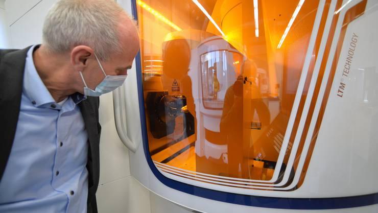 CEO Jürgen Schock betrachtet durch das orange Schutzglas eine Lasermaschine bei der Arbeit.
