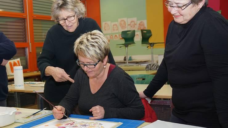 Unter Anleitung von Silvia Merz (links) übt Susanne Gautschi die richtige Pinseltechnik. Elisabeth Schneider schaut zu.