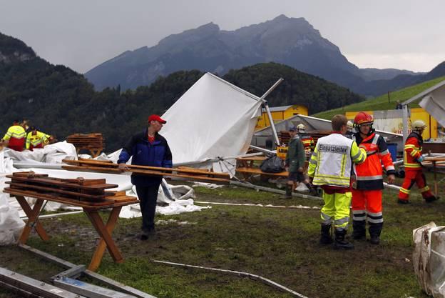 Feuerwehrmänner inspizieren das durch einen massiven Hagelsturm verwüsteten Festareal des traditionellen Allweg Schwinget in Ennetmoos im Kanton Nidwalden