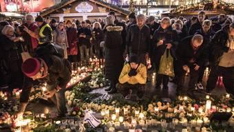 Patrik Müller: «Ihr wichtigstes Ziel haben die Terroristen bislang verfehlt: Unsere freie, offene Gesellschaft hat sich nicht zermürben lassen.» Bild: Ein Jahr nach dem Terroranschlag auf einen Berliner Weihnachtsmarkt gedenken Besucher den Todesopfern.