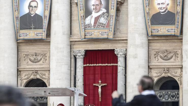 Während der Heiligsprechung von Erzbischof Oscar Romero (l.), Paul VI. (M.) und eines weiteren Seligen prangen deren Grossporträts an der Fassade des Petersdoms.