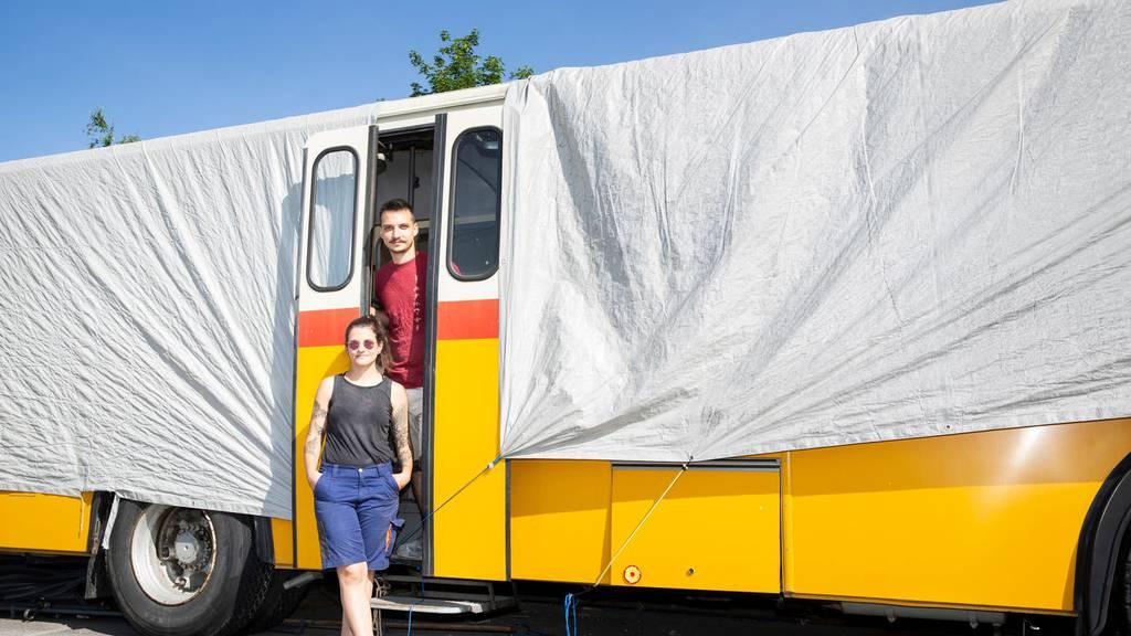 Das ausgehöhlte Postauto unter der Plane: Astrid Dörig und Samuel Rohrhirs stehen vor ihrem Projekt.