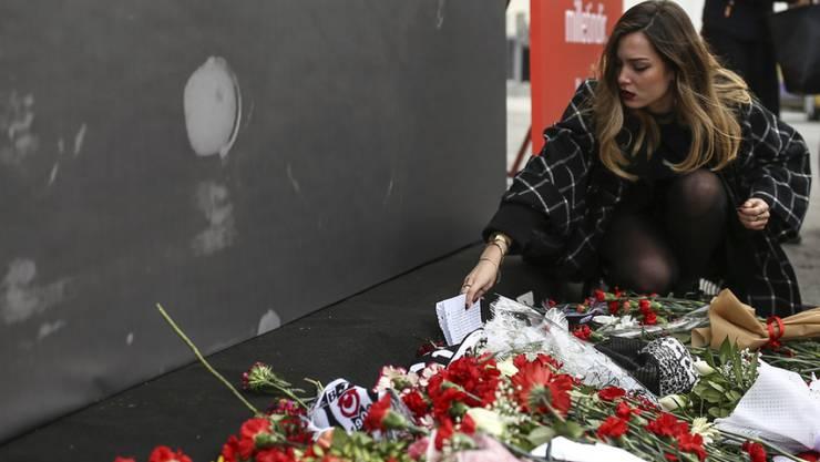 In Gedenken an die Opfer des Doppelanschlags von Istanbul legt eine Frau vor der Vodafone Arena, wo der türkische Fussballverein Besiktas seine Heimspiele austrägt, eine Nachricht nieder.