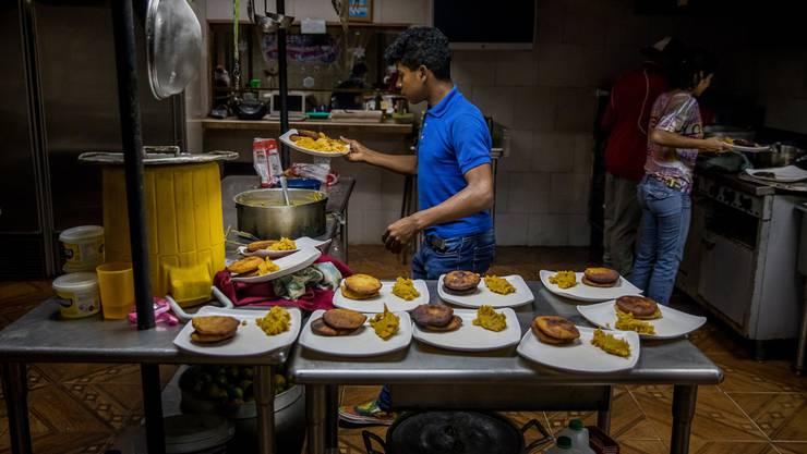 Kinder, die in einem Heim in Caracas leben, weil sie von den Eltern verlassen wurden, bereiten das Nachtessen zu.