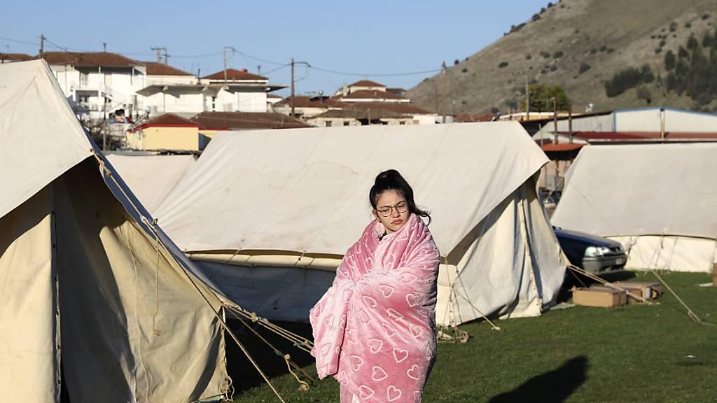 Ein Mädchen steht in eine Decke gehüllt vor Zelten. Nach einem starken Erdbeben in Mittelgriechenland haben viele Menschen die Nacht zum heutigen Donnerstag in Zelten, Hotels und bei Freunden verbracht. Foto: Vaggelis Kousioras/AP/dpa