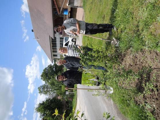 Simone und Reto Hirter mit den Gartenbauern vor der neugepflanzten Wildhecke.