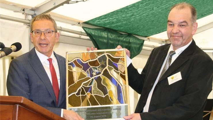 Regierungsrat Urs Hofmann (links) überreicht Gemeindeammann Rolf Häusler eine Kantonswappenscheibe.