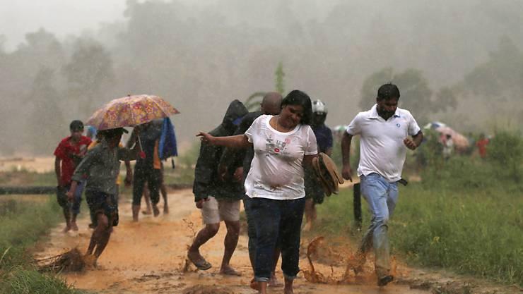 Auch rund um die Hauptstadt Colombo haben die Unwetter Schäden angerichtet - diese Menschen fliehen vor einem Erdrutsch aus ihrem Dorf.