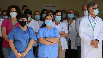 Mitarbeiter des Krankenhauses Virgen de la Victoria in Malaga legen eine Schweigeminute ein. Im von der Corona-Pandemie schwer betroffenen Spanien hat eine zehntägige Staatstrauer für die gut 27 000 Todesopfer der Pandemie begonnen. Der Beginn der Ehrung wurde am Mittwoch um zwölf Uhr mittags von einer Schweigeminute im ganzen Land begleitet. Foto: Álex Zea/EUROPA PRESS/dpa