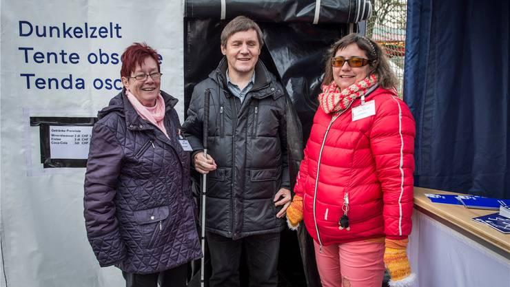 Die Sehbehinderten Ruth Häuptli (l.), Adrian Meury und Verena Müller vor dem Eingang des Dunkelzelts.