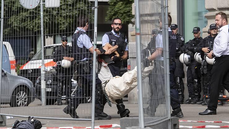 Schwerarbeit für die Staatsgewalt: Polizisten tragen eine Klimaaktivistin vom Eingang der Credit Suisse in Zürich weg.