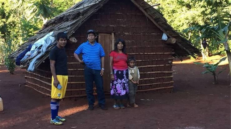 Häuptling Verá Mirí (links) mit einer Familie vor deren Hütte in Tupamba é.