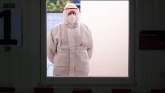 Ein Helfer der Johanniter wartet im Corona Testzentrum am Flughafen Hannover auf den nächsten Patienten. Foto: Julian Stratenschulte/dpa