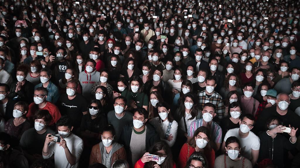Menschen mit Mund-Nasen-Schutzbedeckung besuchen ein Konzert in Barcelona. Foto: Emilio Morenatti/AP/dpa