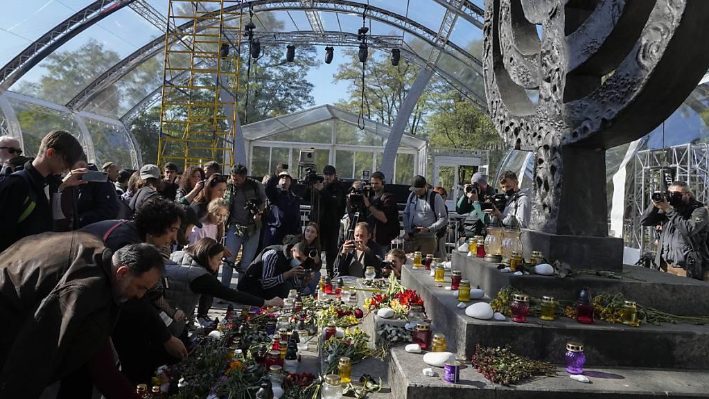 Menschen beten an einer Gedenkstätte für die Opfer des Massakers an jüdischen Bürgern in Babyn Jar (Altweiberschlucht). Die Babyn-Jar-Gedenkstätte hat 80 Jahre nach dem Massaker eine erste Liste mit 159 Beteiligten an dem von Deutschen in der Ukraine verübten Verbrechen veröffentlicht. Foto: Efrem Lukatsky/AP/dpa
