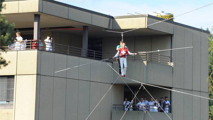 Hochseilartist Freddy Nock führt Spital-CEO Christian Reize vom 5. Stock des Spitals auf das Dach des neuen Rehazentrums...