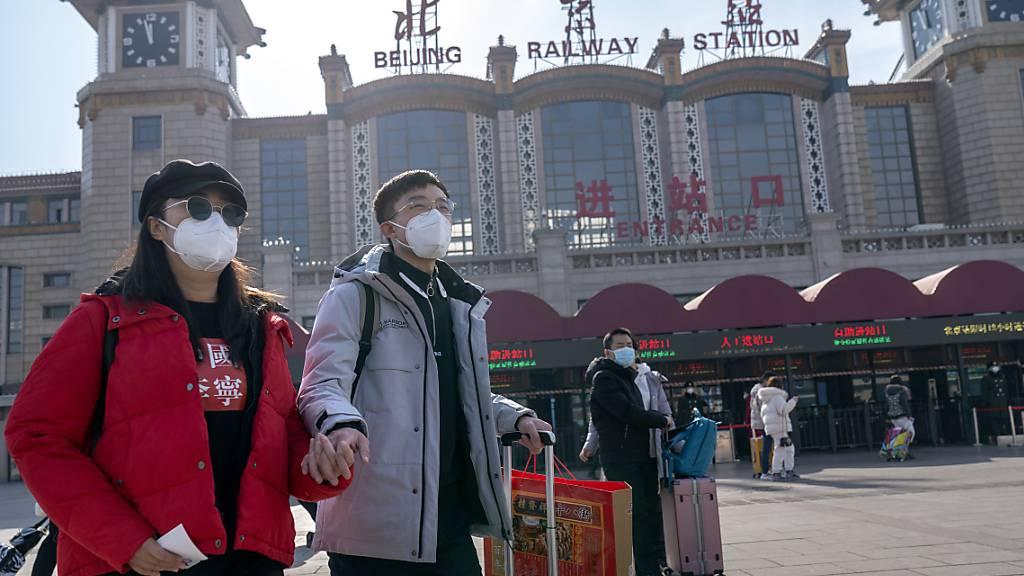 Passagiere, die als vorbeugende Maßnahme gegen die Verbreitung des Coronavirus Mund-Nasen-Bedeckungen tragen, gehen mit ihrem Gepäck vor dem Pekinger Bahnhof entlang. Foto: Mark Schiefelbein/AP/dpa