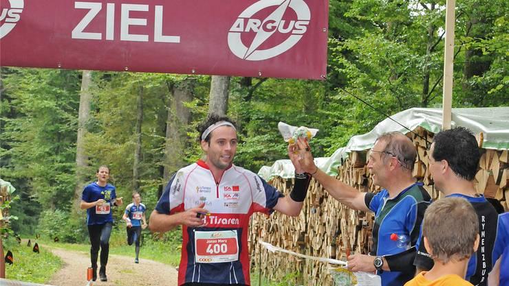 Gesamtsieger Jonas Merz hat im Zieleinlauf Zeit, seinen Vater Osi abzuklatschen.
