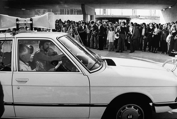Der Solothurner Polizeidirektor Godi Wyss (SP) spricht über das Mikrofon aus dem Dienstwagen zu den Besetzern der Zufahrt zum AKW Gösgen. (Beim Parkzentrum Däniken, 1977)