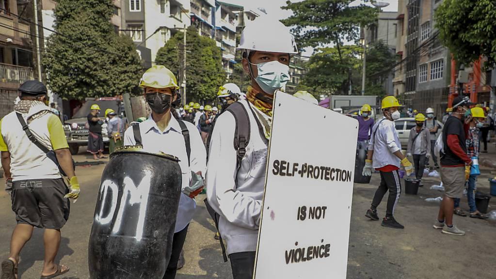 Anti-Putsch-Demonstranten mit Helmen halten währende eines Protests behelfsmäßige Schilder mit der Aufschrift «Self protection is not violence» (Selbstschutz ist keine Gewalt). Foto: Str/AP/dpa