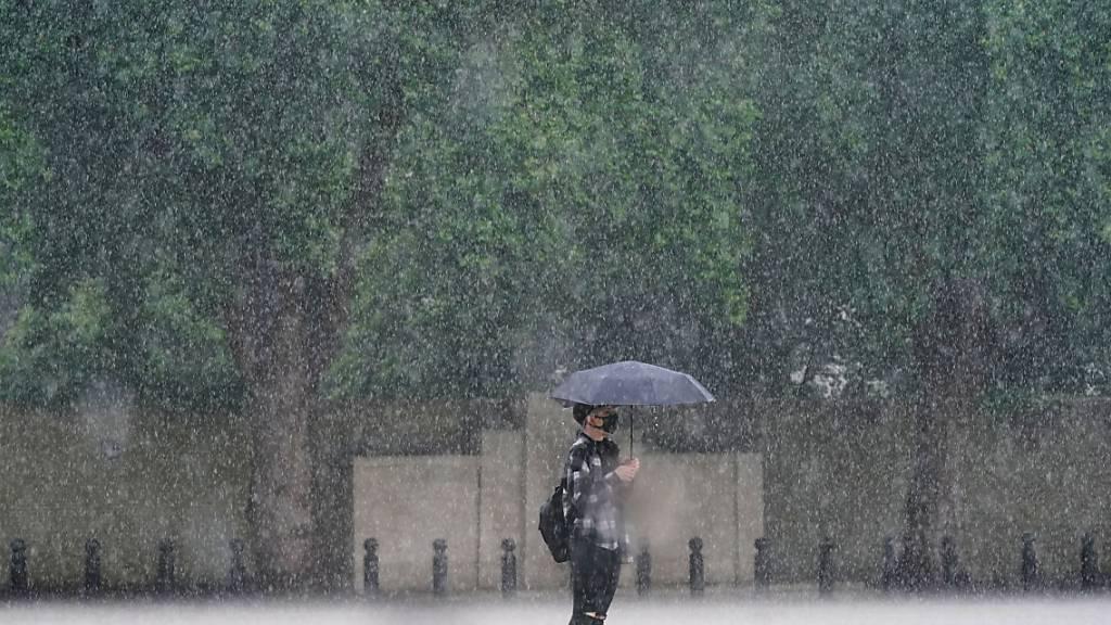 Eine Frau in London schützt sich mit einem Schirm vor dem starken Regen. Foto: Victoria Jones/PA Wire/dpa