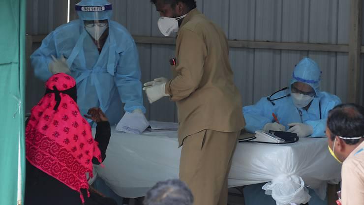 """Ein indischer Arzt spricht mit einer Frau mit Covid-19-Symptomen in der Anmeldestelle des Krankenhauses """"Government Fever Hospital"""". Foto: Mahesh Kumar A/AP/dpa"""