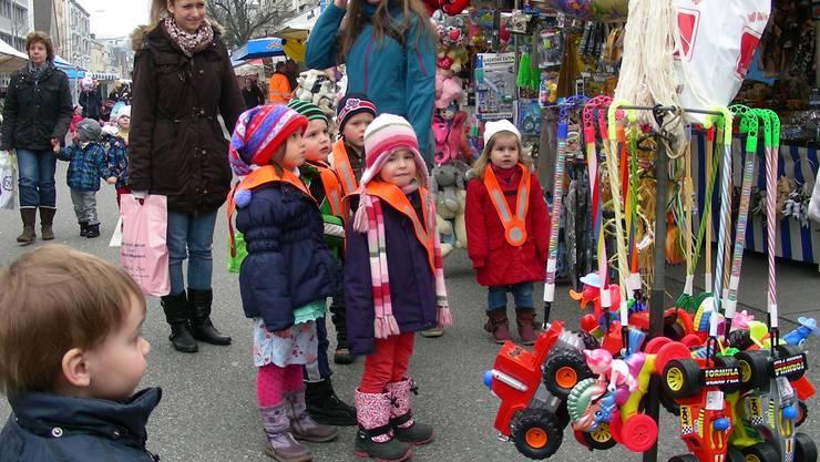 Kinder bestaunen Spielzeuge auf dem Markt in Wettingen. DM