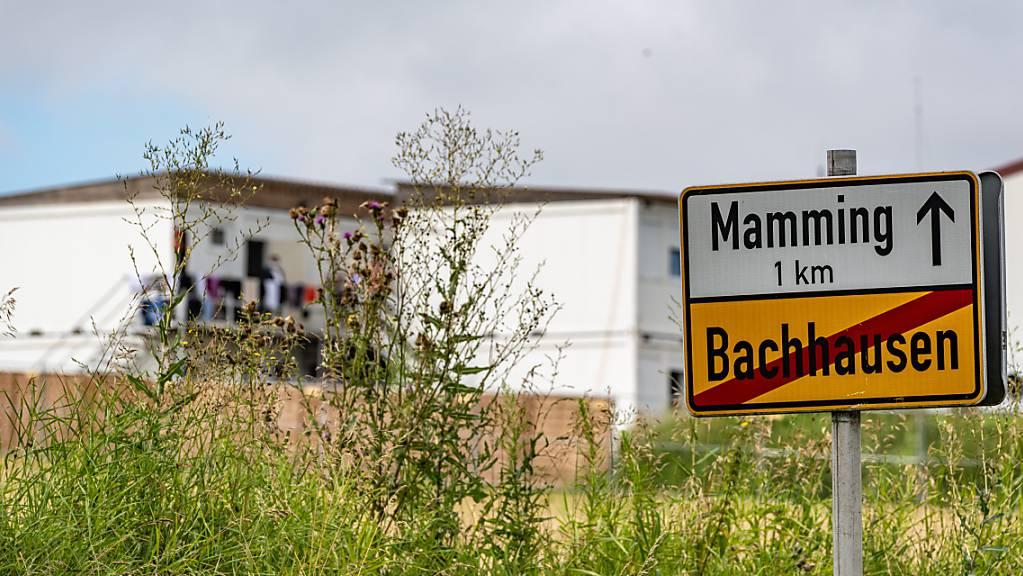Das Ortsschild von Mamming, im Hintergrund sind die Unterkünfte von Erntehelfern zu sehen. Foto: Armin Weigel/dpa