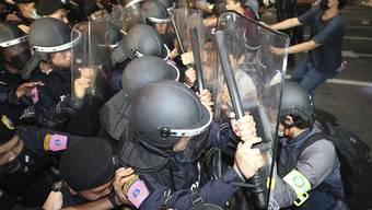Pro-demokratische Demonstranten stoßen während eines Protests mit Polizisten zusammen. Foto: Rapeephat Sitichailapa/AP/dpa