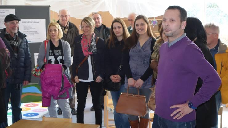 Schulpflegepräsident Rainer Kirchhofer, mit violettem Pullover, informeirt die Besucher über das Projekt.
