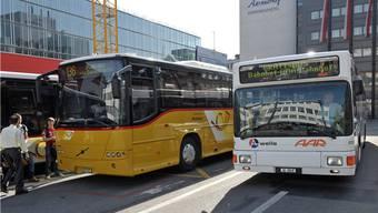 Gelbe Postautos fahren weiterhin auch in Aarau, hier vor dem Bahnhof. Daneben ein weisser Bus der regionalen Verkehrsbetrieb AAR bus+bahn.