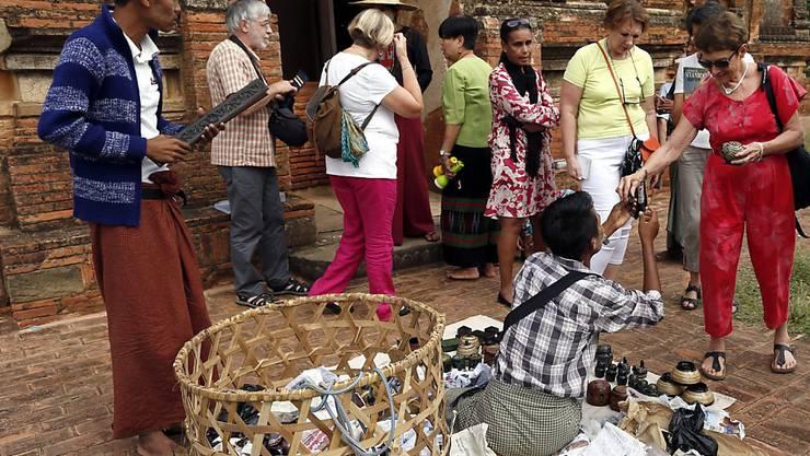 Touristen kaufen Souvenirs vor dem Tham Bula Tempel in Bagan. Künftig dürfen sich Urlauber nicht mehr uneingeschränkt auf dem Gelände von Bagan bewegen: Die Regierung Myanmars hat die an Pagoden reiche Ebene zum Welterbe angemeldet (Archiv).