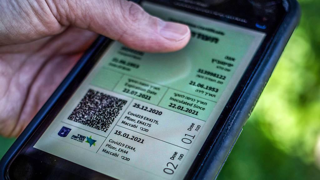 ARCHIV - Ein israelischer Mann hält ein Smartphone in der Hand, auf dem der sogenannte «Grüne Pass» abgebildet ist. Foto: Ilia Yefimovich/dpa