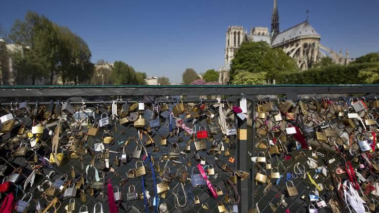 Vorhängeschlösser an einer Seine-Brücke als Zeichen ewiger Liebe.
