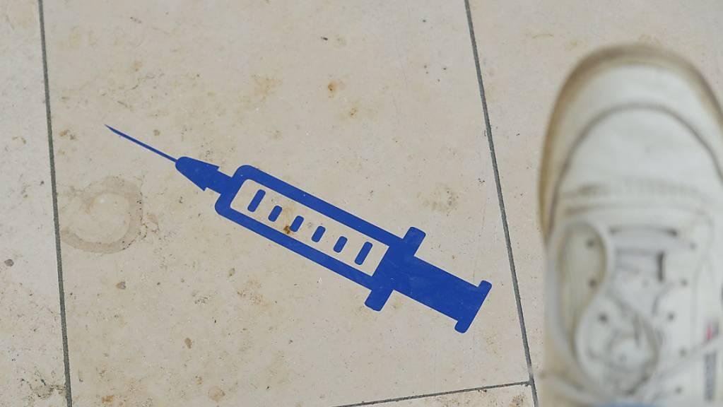 Das Symbol einer Spritze ist auf dem Boden der Muldentalhalle in Sachsen aufgeklebt.