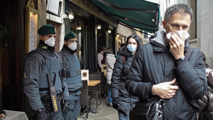 In Venedig tragen Polizisten und Passanten am Tag des Karnevals Schutzmasken. Vielerorts waren sie ausverkauft. Bild: Abir Sultan/EPA (Venedig, 23. Februar 2020)