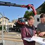 Messeleiter Mike Zettel (rechts) mit Elektriker Janick Heim, Servicemonteur bei Bouygues Energies & Services. Im Hintergrund wird gerade ein nigelnagelneues Pistenfahrzeug für den Stand der Gastregion UNESCO Biosphäre Entlebuch angeliefert.