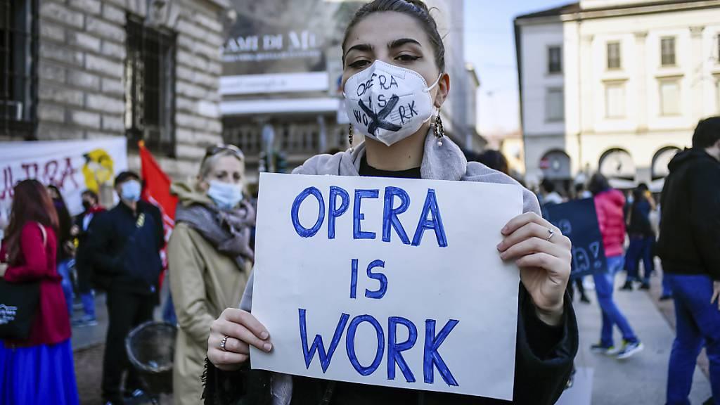 Eine Frau mit Mundschutz hält bei einer Demonstration gegen die Maßnahmen der Regierung zur Eindämmung der Corona-Pandemie ein Schild mit der Aufschrift «Opera is work» (zu deutsch: «Oper ist Arbeit») in den Händen. Foto: Claudio Furlan/LaPresse/AP/dpa