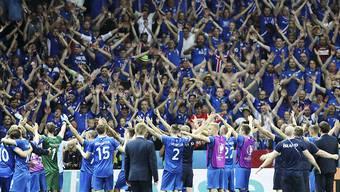 Islands Spieler feiern mit ihren Fans nach dem Sieg gegen England