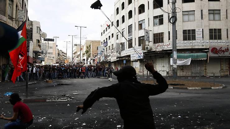 Ein palästinensischer Jugendlicher schleudert einen Stein gegen israelische Soldaten in Hebron