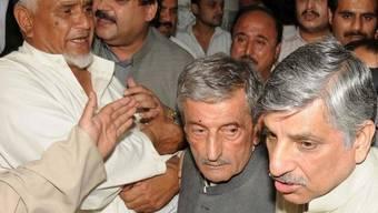 Der in Peshawar verletzte Parteiführer Ghulam Ahmed Bilour (Mitte) nach dem Anschlag