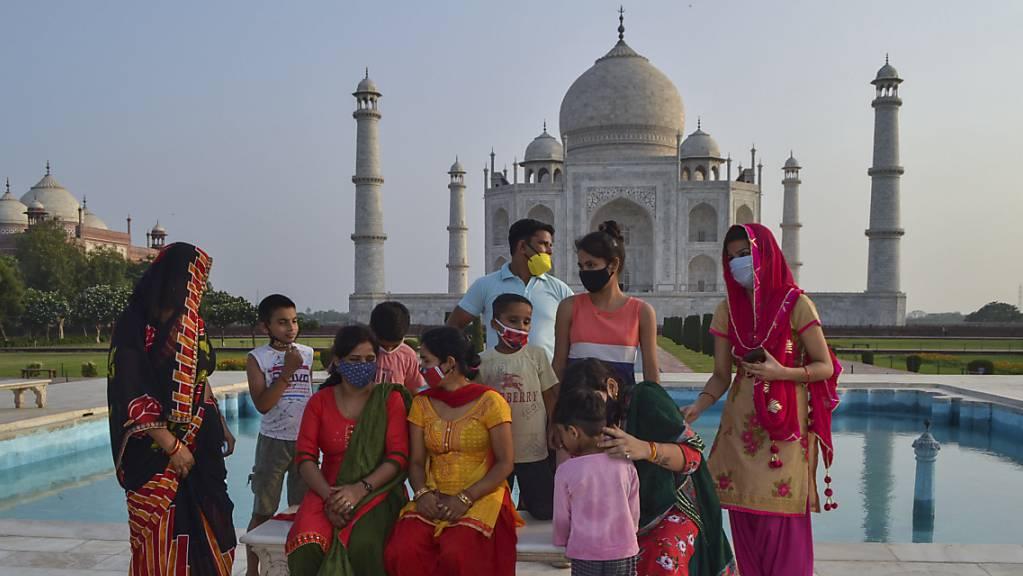 Eine Gruppe von Touristen sitzen auf einer Bank am Wasserbecken vor dem Mausoleum Taj Mahal. Aufgrund des Rückgangs von Corona-Neuinfektionen öffnet die Regierung in Indien mehrere Denkmäler.