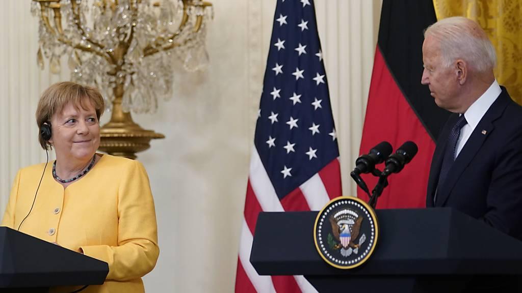 Bundeskanzlerin Angela Merkel (CDU, l) lächelt während US-Präsident Joe Biden bei einer Pressekonferenz im Weißen Haus spricht. Foto: Susan Walsh/AP/dpa