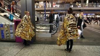 Eingehüllt in Rettungsdecken stehen Aktivisten von Amnesty Schweiz im Bahnhof Bern.